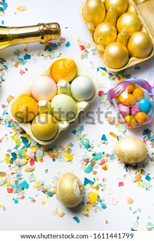 Box with  colored eggs, easter conceptual image,golden bottle of champagne, pieces of eggshell spread over a white background, easter conceptual image, flat lay composition hard natural direct light