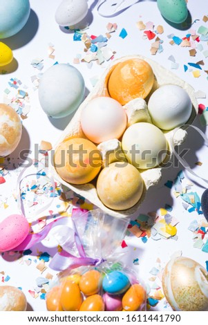 Box with  colored eggs, easter conceptual image,pieces of eggshell spread over a white background, easter conceptual image, flat lay composition hard natural direct light