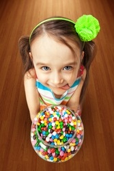 Box with colorful candies in the hands of little girl