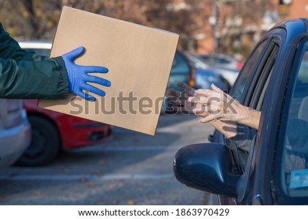 box with essential supplies given to elderly person at food distribution point queue Stock photo ©