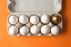 Box with golden egg among white ones on color background. Concept of uniqueness