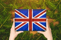 Box with Great Britain flag in female hands. Fir branches on the background
