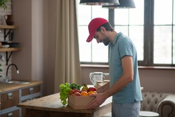 Box with groceries. Man in a red hat putting the box with groceries on the table