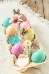 Box with pastel-colored easter eggs, candles in eggshells and spring flower blossoms as Easter decoration