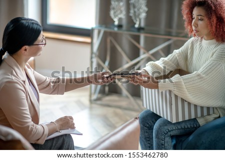 Box with photos. Depressed curly woman bringing box with photos to psychoanalyst