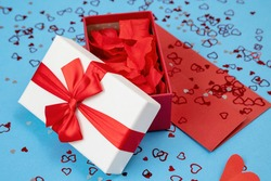 Box with ribbon filled with rose leaves on red envelope. Open present with postcard lying on blue background. Love letter with gift and sequins around.