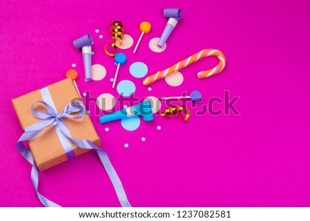 Box with splashed confetti of ribbon, dudes and other festive accessories