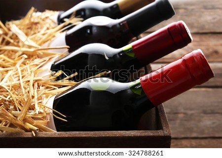 Box with straw and wine bottles on wooden background Stock photo ©