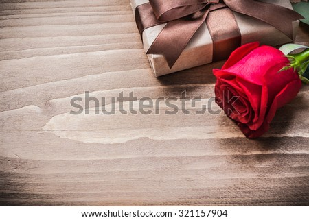 Boxed present expanded rose head on wooden board holiday concept.