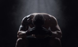 Boxer athlete sits with a drooping head on a black background