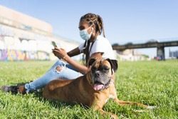 Boxer dog next to an african woman with braids and a mask sitting on the grass using her mobile phone on a sunny day