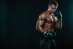 Boxer, man fighting or posing in gloves on black background. Fitness and boxing concept. Individual sports recreation.