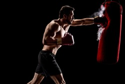Boxer punching a bag with dust particles coming out over a black background