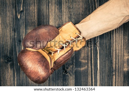 Boxer's hand with leather boxing glove near wood grunge background