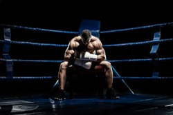 boxer sitting and recreation on boxing ring, black background, horizontal photo