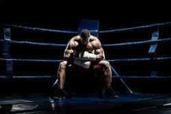 boxer sitting and recreation on boxing ring, black background, horizontal photo