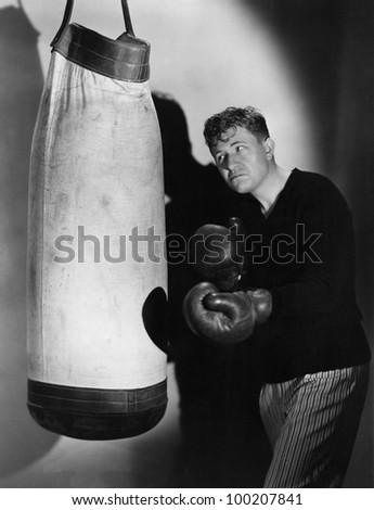Boxer using punching bag - stock photo