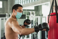 Boxer with corona virus protection by green face mask punch red sandbag by black boxer glove. Exercise workout training during quarantine in sport gym