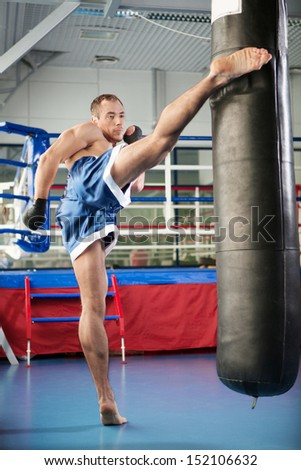 Boxer. Young confident kickboxer training at the punching bag