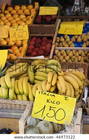 Boxes of bananas and other fruits at a market in Italy. Vertical shot.