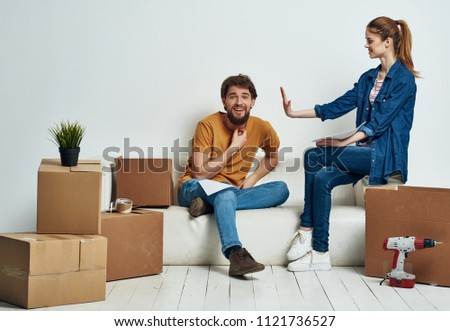 boxes scattered around the room and young people on the couch                             #1121736527