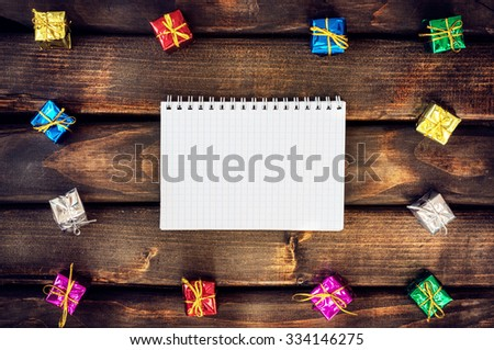 Boxes with gifts on a dark wooden boards. White notepad. Happy new year. Space for text. Old background. New Year background. Christmas. Xmas. Noel.