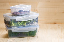 boxes with raw vegetables for stocking up, home food storage in plastic containers, on wooden background