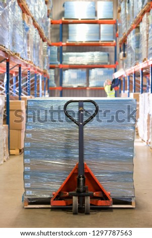 Boxes wrapped in polythene on pallet truck in distribution warehouse