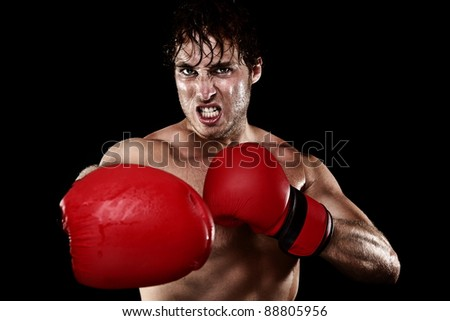 Boxing boxer. Man with boxing gloves hitting and punching looking angry. Strong muscular fit fitness model showing competition strength. Caucasian male model isolated on black background.