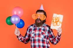 boxing day. happy birthday to you. male holiday celebration. bearded guy with party balloons and gift box. unshaven brutal man with beard celebrate business success. express pure happiness