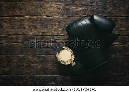 Boxing glove and golden medal award trophy on a wooden table background with copy space. Box champion concept. #1311704141