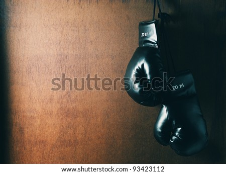 Boxing glove hanging on wooden grunge background