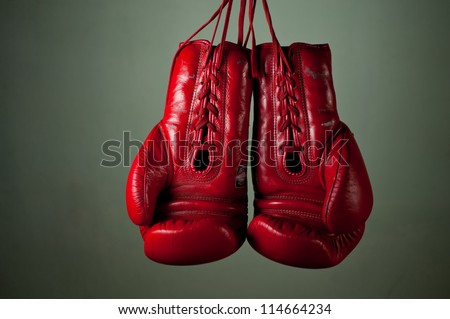 Boxing gloves hanging from laces on a grey background.