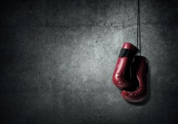 Boxing gloves hanging nailed to wall as concept of retirement