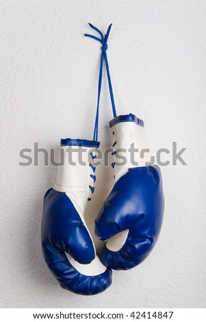 Boxing gloves hanging on a white wall