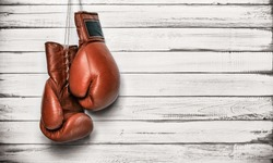 Boxing gloves hanging on wooden wall