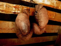 Boxing gloves on the wall. Old, vintage pair of leather mittens hangs on the wood wall. Red colors and soft lights. Gloves of retired boxer and fighter. It hangs on a nail in a barn or rustic house.