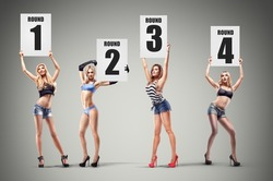 Boxing ring girls holding a board with round number. set. High resolution