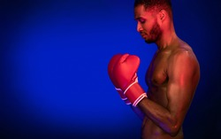 Boxing Sport. African Boxer Guy Wearing Gloves Ready To Fight On Ring Posing On Blue Studio Background. Free Space, Side-View