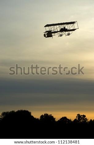 Boxkite plane flying at sunset