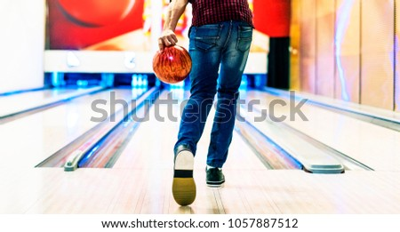 Boy about to roll a bowling ball hobby and leisure concept #1057887512