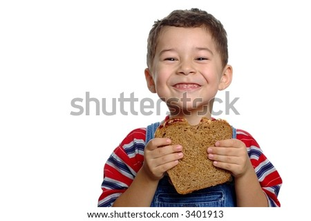 Boy aged five years with peanut butter and jelly sandwich on whole wheat bread, isolated on white background