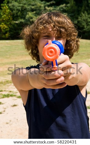 boy aiming water gun at you