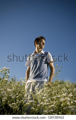 Boy among a field of daisies, with a clear blue sky as background and a peaceful atmosphere.