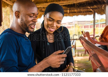 boy and a girl looking at something on a mobile phone. two people viewing something interesting on a phone, girl is smiling with her hair covered