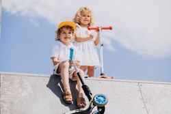 Boy and a girl riding scooter together in park