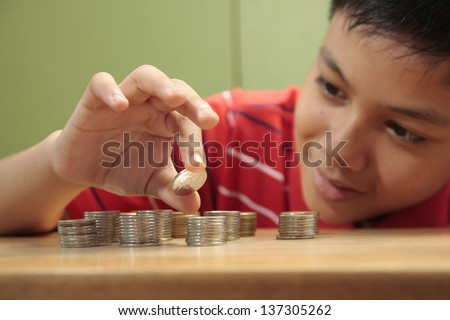 Boy and a Pile of Coins A photo of a boy looking at a stack of coins and stacking them. - stock photo