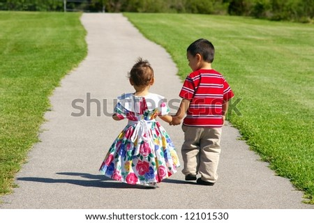 Boy and baby girl walking on a sidewalk