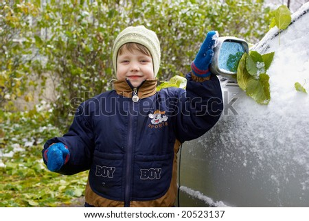 Boy and car in autumn park with first snow