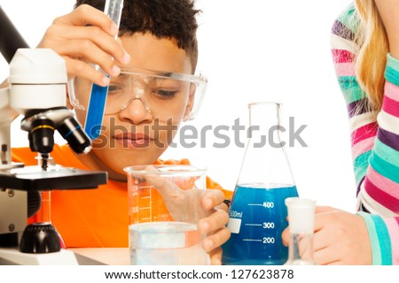 Boy and chemistry - 8 years old mixing liquids in test tubes and flasks